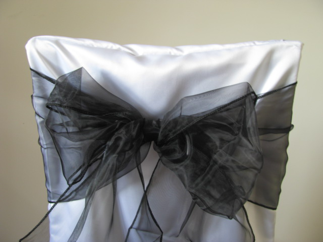 white chair covers and black sashes