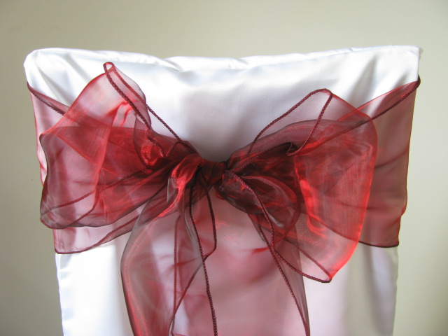 white chair covers and burgundy sashes