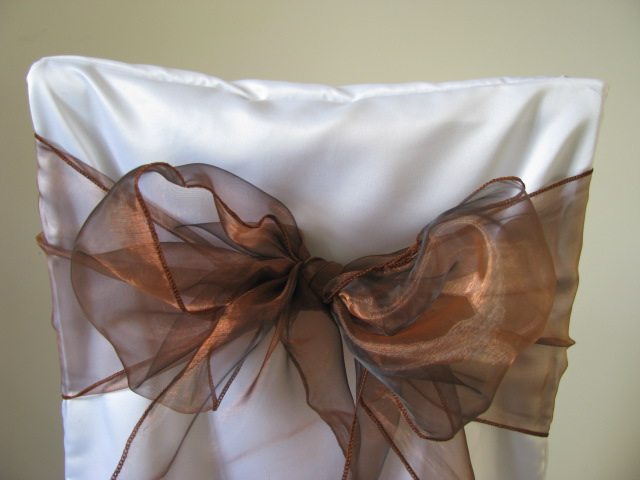 white chair covers and chocolate sashes