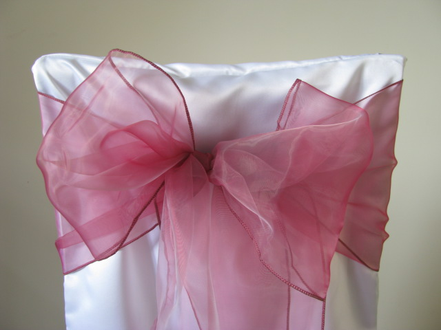 white chair covers and dusty pink sashes