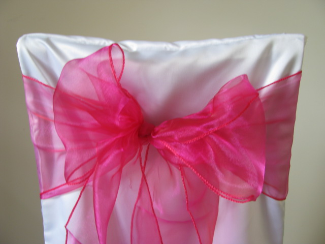 white chair covers and fuschia sashes