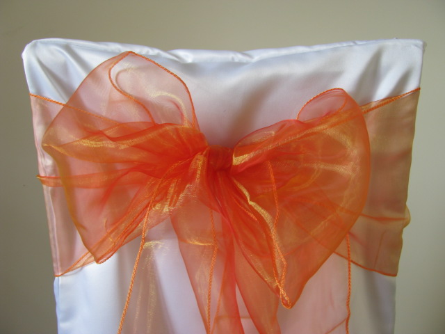 white chair covers and orange sashes
