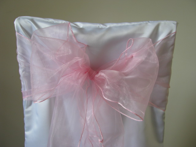 white chair covers and pale pink sashes