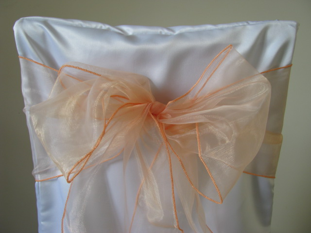 white chair covers and peach sashes
