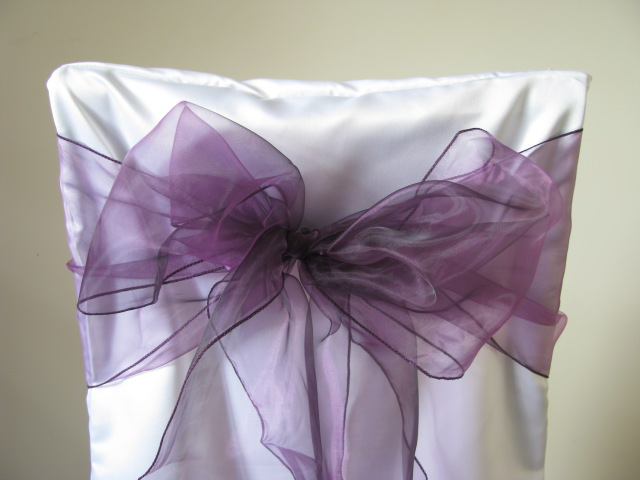 white chair covers and purple sashes