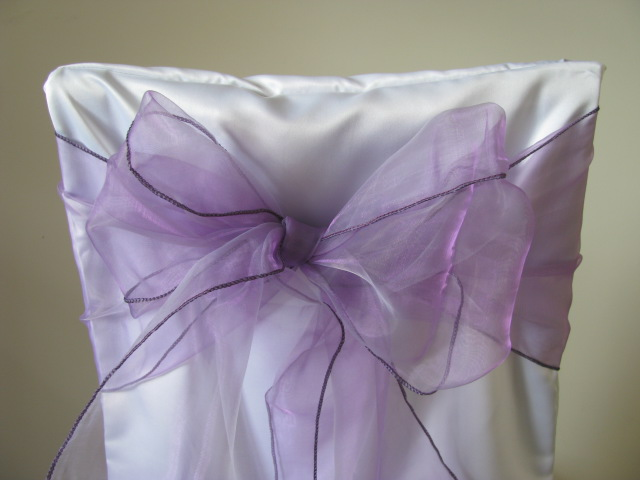 white chair covers and violet sashes